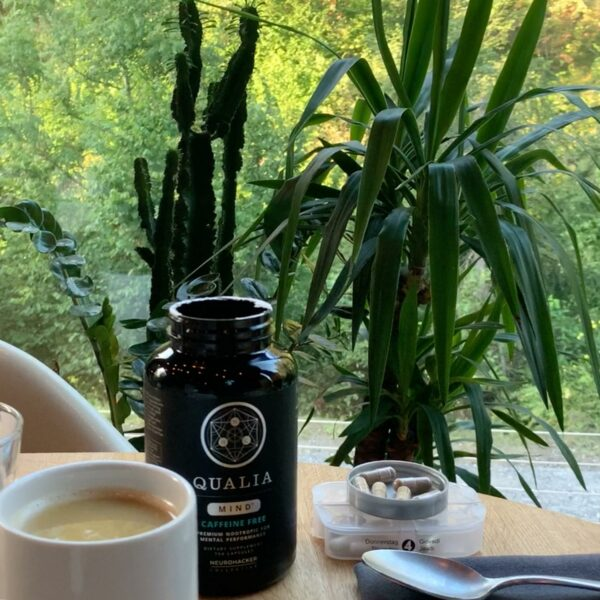 A bottle of Qualia Mind Caffeine Free on a table next to a cup of coffee and some pills