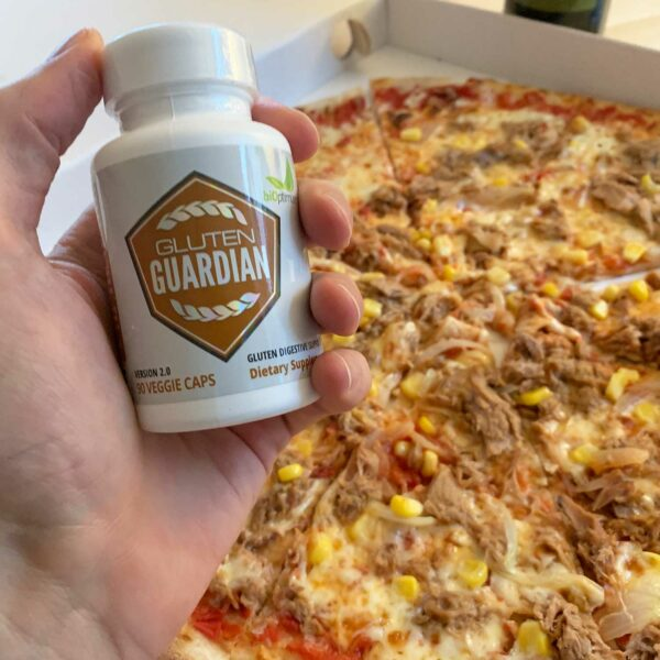 A hand holding a bottle of gluten guardian infront of a tuna pizza
